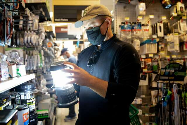 Ethan Tyler of Tam Valley shops for high-powered lanterns to help light his son's birthday gathering while shopping at Goodman Building Supply in Mill Valley on Oct. 24, ahead of a planned PG&E power shut-off.