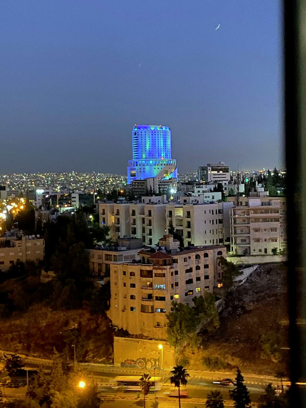 The view out the hotel window in downtown Amman with Le Royal Hotel in the distance lit up in blue.