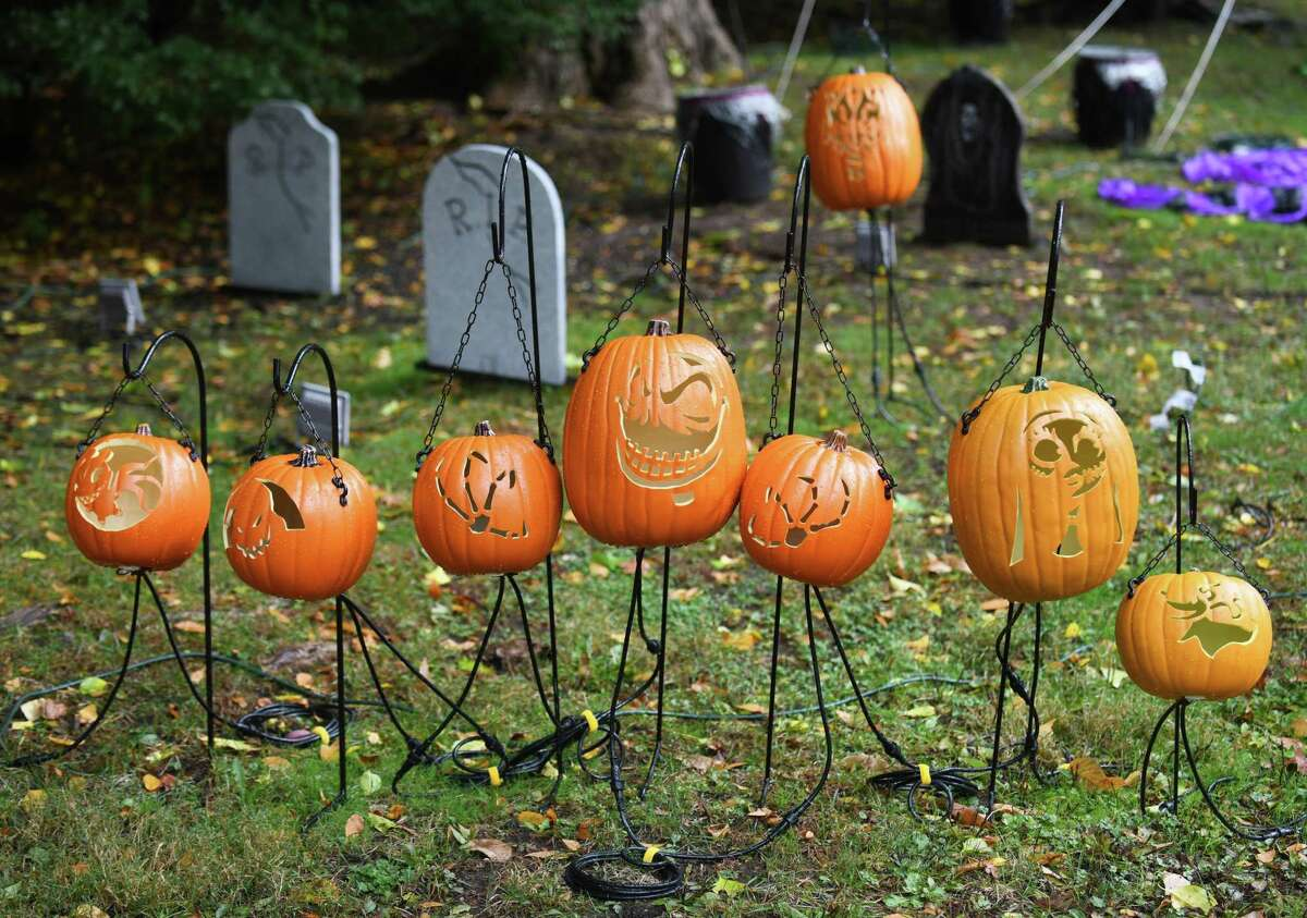 Fifty-seven carved pumpkins are displayed in front of a home on Pepper Ridge Road in Stamford, Conn. Wednesday, Oct. 28, 2020. Gabriel Sgandurra, 19, and Sabrina Sgandurra, 16, started carving the 57 pumpkins over the summer and their father, Robert, arranged them to be illuminated at night.