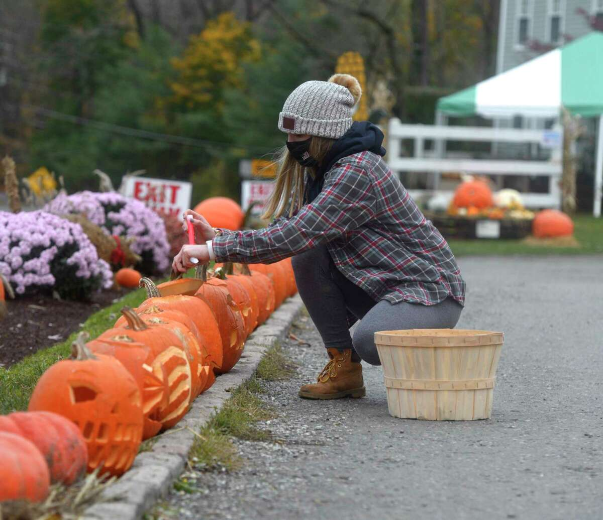 Sydney Yorio drops a glow stick into a carved pumpkin on display as Halas Farm tries to beat the Guinness World Record for the most carved pumpkins. Friday, October 30, 2020, in Danbury, Conn.