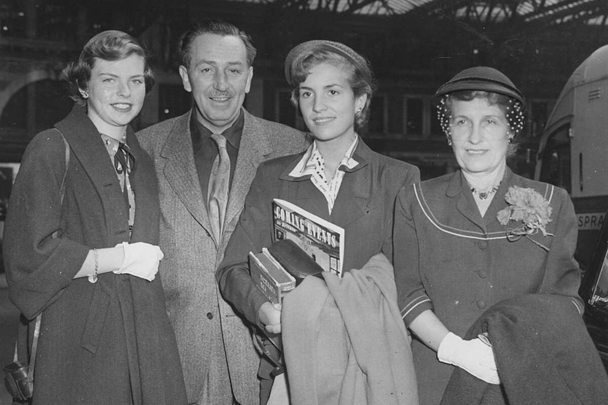 Walt Disney with his wife and daughters at Waterloo station after arriving on the Queen Mary boat train