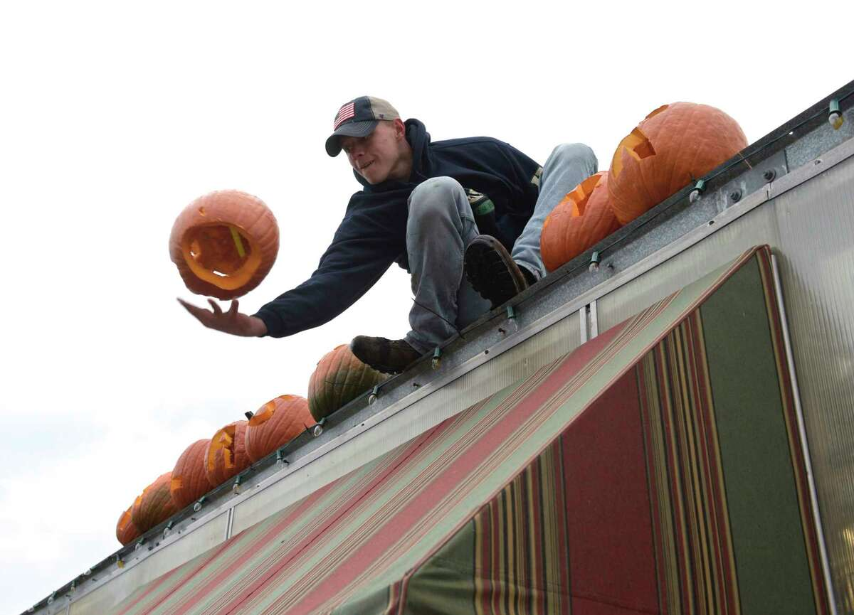 """Michael Halas reaches out to grab a pumpkin that was tossed up to him as he arranged a group that spelled out """"Halas Farm"""" on a roof. The farm is looking to beat the Guinness World Record for the most carved pumpkins. They are on display for drive-by viewing Friday and Saturday nights. Friday, October 30, 2020, in Danbury, Conn."""