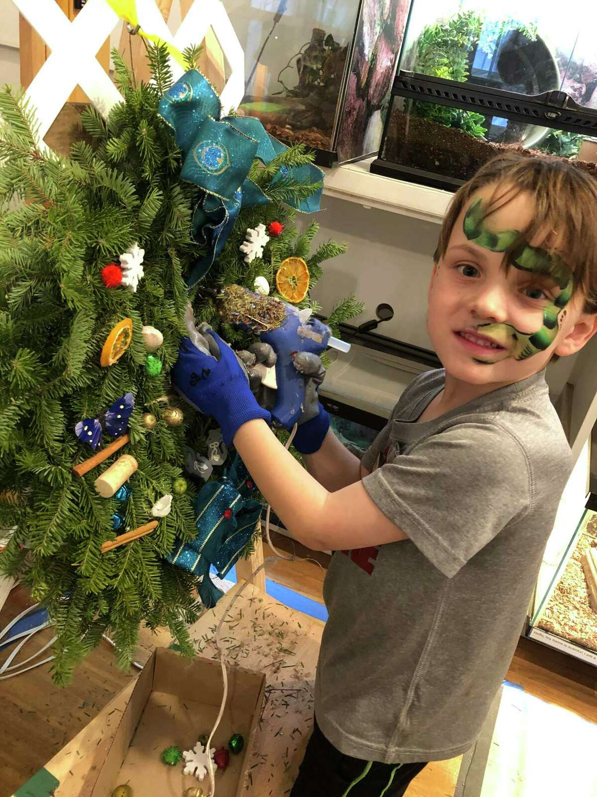 Grey Herbst, 7, of Wilton, decorates a wreath at Woodcock Nature Center's Wreath Festival last year.