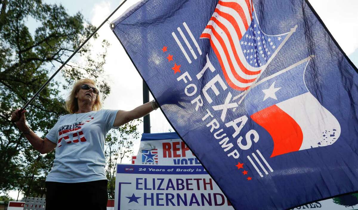 Montgomery County Republican Party Precinct 98 Chairman Neda Henery waves a flag showing support for President Trump in front of the early voting location at the South Montgomery County Community Center, Wednesday, Oct. 21, 2020, in The Woodlands.
