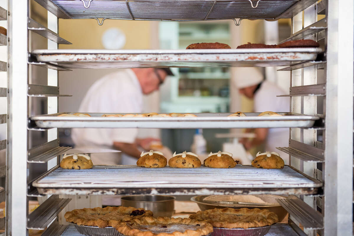Owner Joe Schuver prepares bakery items behind the counter of Destination Baking Company.