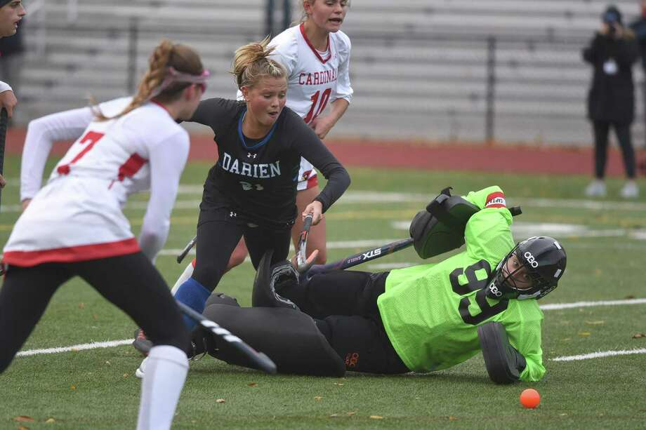 Greenwich goalie Jorja Pastore slides out to block a shot from Darien's Mully McGuckin during the Blue Wave's 2-0 victory on Friday in Greenwich. Photo: David Stewart / Hearst Connecticut Media / Connecticut Post