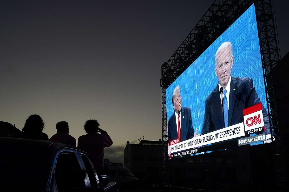 People at Fort Mason Center in San Francisco watch a big screen from their vehicle as President Trump and Democratic presidential candidate Joe Biden debate.