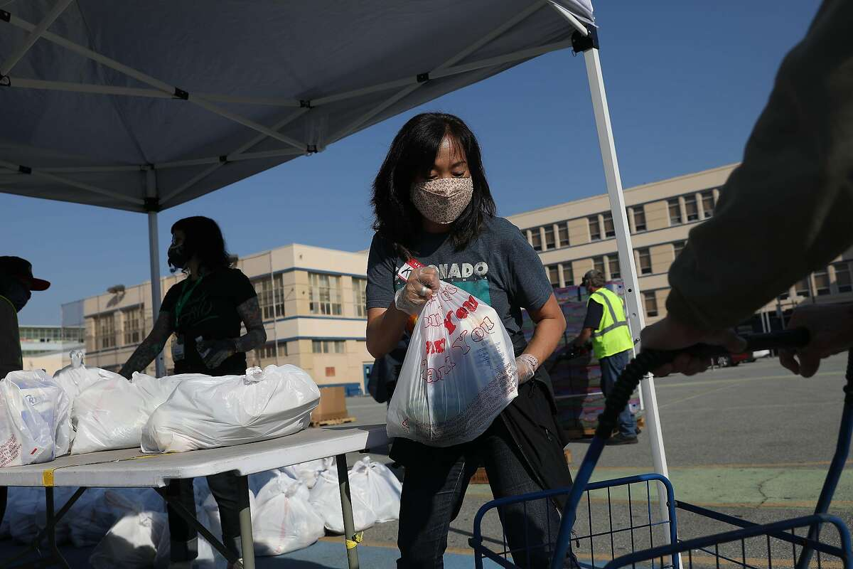 Volunteer Kim Langworthy, of San Francisco, places bags of groceries into a cart as she works at the San Francisco-Marin Food Bank pop-up food pantry at Denman Middle School on Wednesday, October 28, 2020 in San Francisco, Calif.