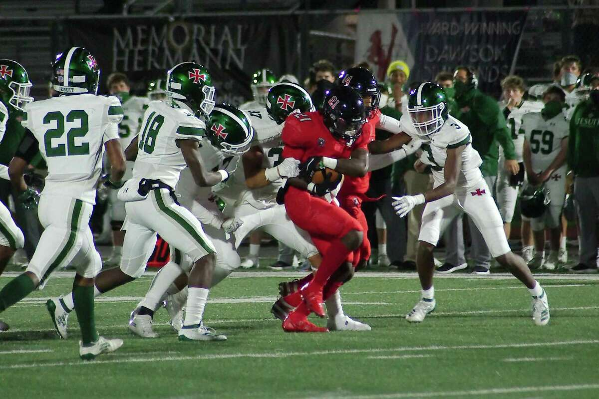 Dawson's Jaden Stewart (21) fights for yardage as he drags Strake Jesuit tacklers Friday, Oct. 30 at The Rig.