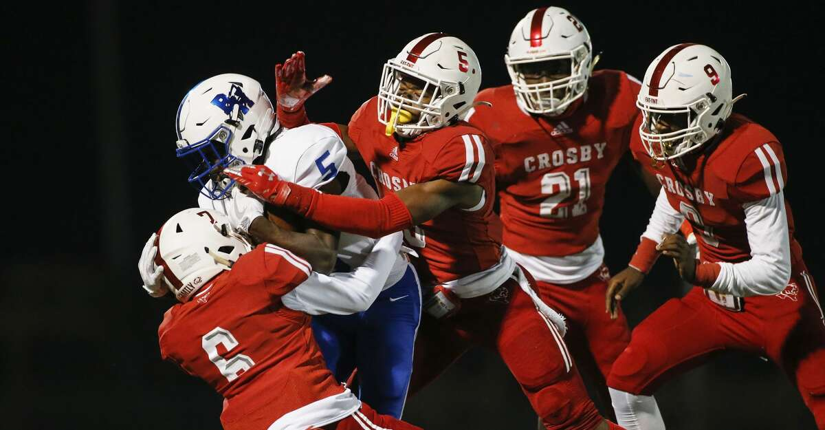 Crosby Cougars Michael Ray (5) and Randolph Hubbard (7) tackle the Barbers Hill Eagles running back during the first half of the high school football game between the Crosby Cougars and the Barbers Hill Eagles at Cougar Stadium in Crosby, TX on Friday, October 30, 2020. The Cougars lead the Eagles 20-7 at halftime.