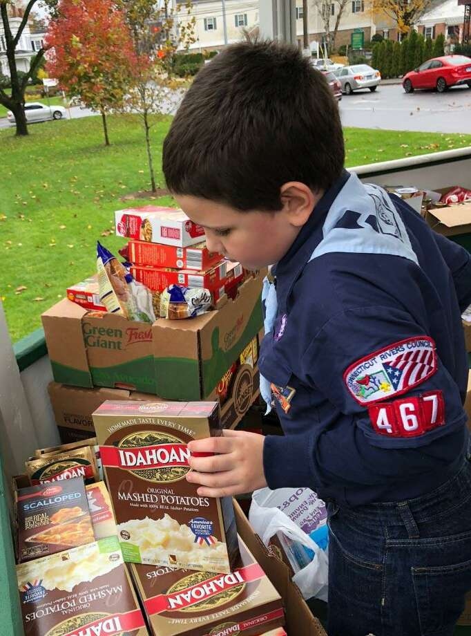 "The Woman's Club of Greater New Milford and the United Way of Western Connecticut will hold a food drive, ""Operation Thanksgiving,"" Nov. 7 near the bandstand on the Village Green. Above, Scout Nathan Brennen assists the group by checking expiration dates on donated goods during the 2018 event. Photo: Deborah Rose / Hearst Connecticut Media / The News-Times  / Spectrum"