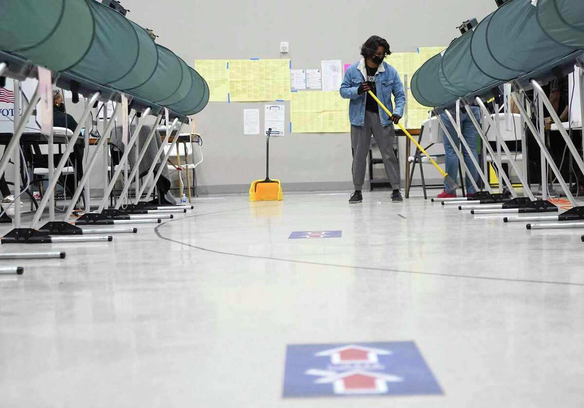 A poll worker sweeps the floor at Victory Houston polling station in Houston on Thursday, Oct. 29, 2020. The location was one of the Harris County's 24-hour locations.