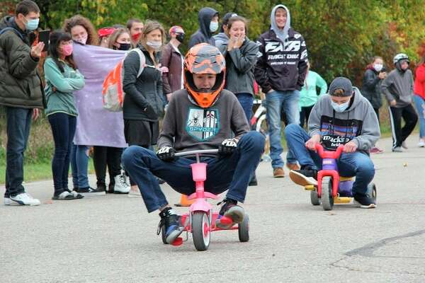 Freshmen Tyler Geilhart and Cemeron McCormick race on their tricycles as the High School watches from a distance.(Submitted Photo)