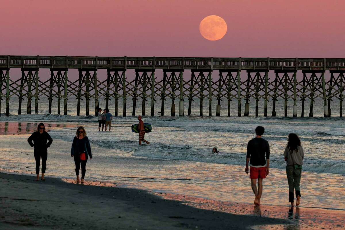 Beachgoers watch as a Waxing Gibbous Moon rises on October 30, 2020 in Folly Beach, South Carolina. The Blue Moon that will rise Saturday will be the first full moon seen in all U.S. time zones on Halloween since 1944.