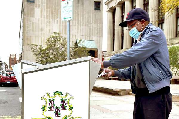 New Haven, Connecticut - Monday, October 25, 2020: Ollie Lawrence of New Haven drops his vote into the State of Connecticut Official Ballot Drop Box in front of the Hall of Records on Orange Street in New Haven.