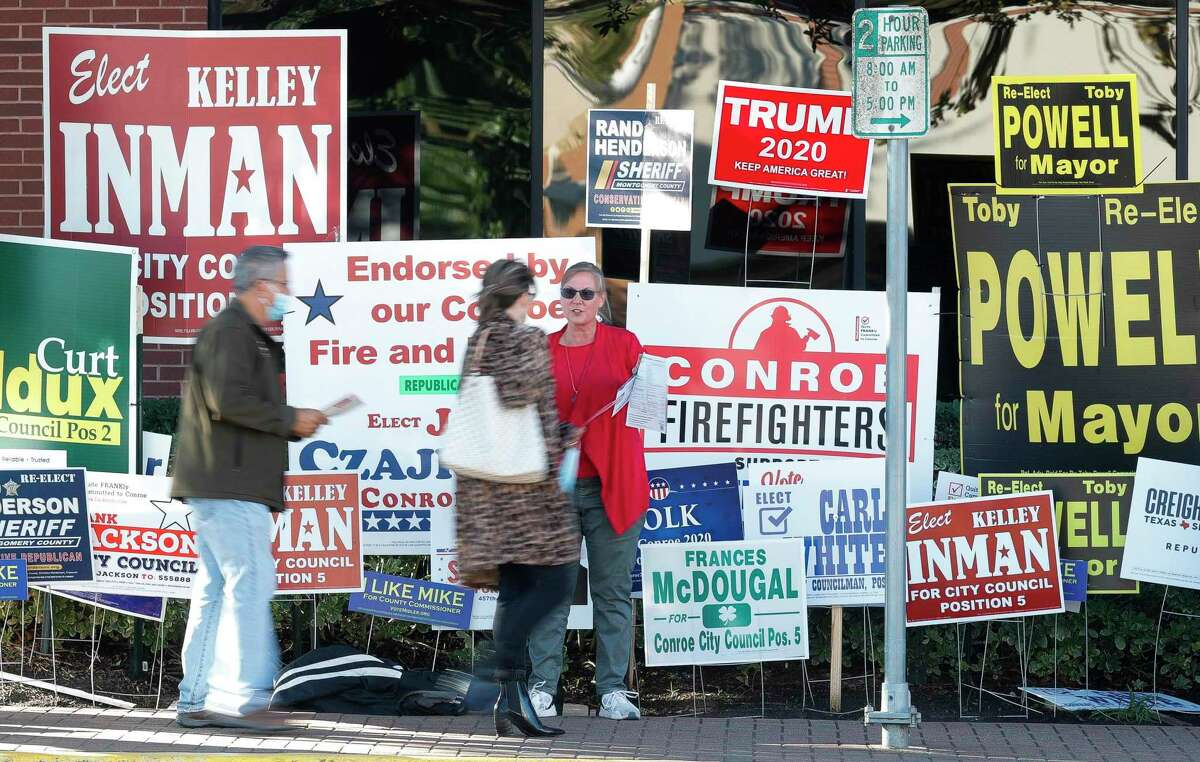 Voters pass by political signs and supporters on their way the polls on the last day of early voting, Friday, Oct. 30, 2020, in Conroe.