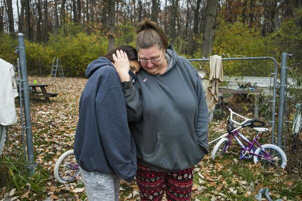 Theresa Ouda, a client of Cancer Services of Midland, right, embraces her daughter, Nuru, 16, left, as Home Depot staff deliver wood pellets and other donated items to the family's home Friday, Oct. 30, 2020. (Katy Kildee/kkildee@mdn.net)