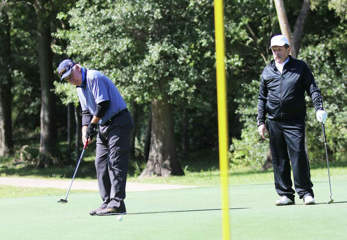 Jeff Skinner watches as John Polasek tries to sink his putt on one of the holes at Blackhorse Country Club last Thursday at the Adam J. Skinner Golf Tournament.