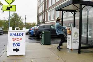 A Greenwich resident places her ballot in the drop box outside Town Hall in Greenwich, Conn. Wednesday, Oct. 28, 2020.