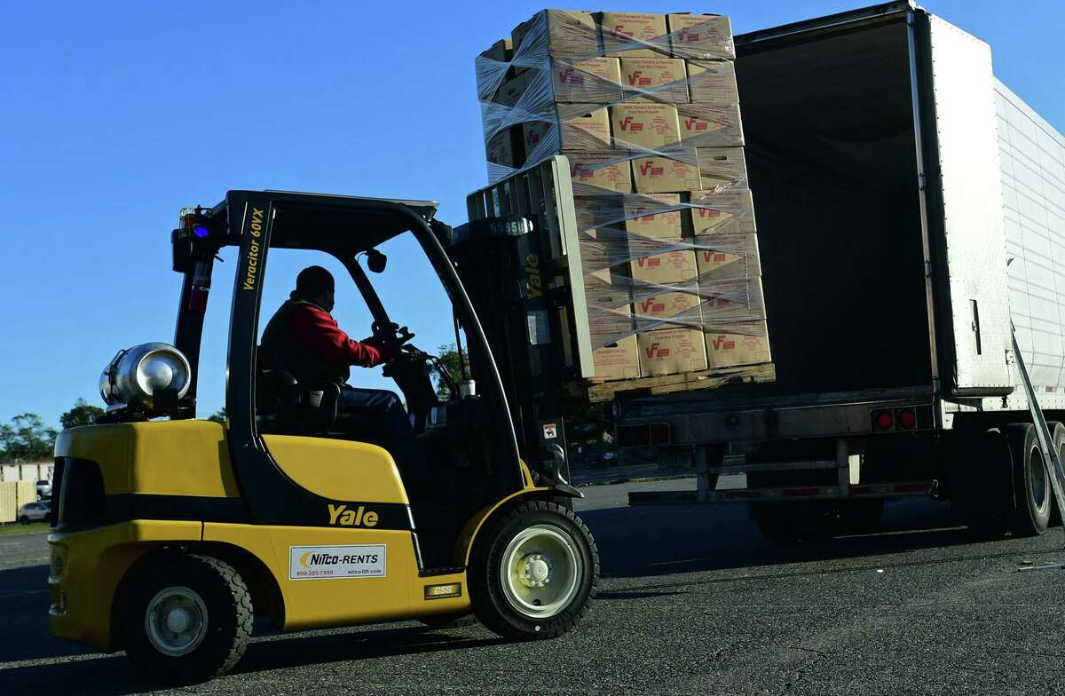 Volunteers help distribute 1,000 boxes of food to local nonprofit and faith-based organizations to help feed the needy Thursday, October 8, 2020, at the distribution point at Andrews Field in Norwalk, Conn. The food is from the USDA, and two tractor-trailers arrived at Andrews Field early Thursday. DPW staff and volunteers from organizations throughtout Norwalk including Stew Leonard's and Keystone Community Church who unloaded the pallets of food and distributed the USDA Farmers to Familes Food Boxes to the organizations to benefit their clients or congregation.