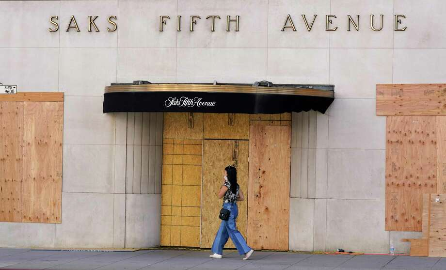 A pedestrian passes a boarded up entrance at the Saks Fifth Avenue store, Friday, Oct. 30, 2020, in Beverly Hills, Calif. Retailers, including Nordstrom, Tiffany and Saks Fifth Avenue, are boarding up their windows and planning to add extra security personnel in some of their locations ahead of the contentious presidential election on Tuesday. Photo: Chris Pizzello, AP / Invision