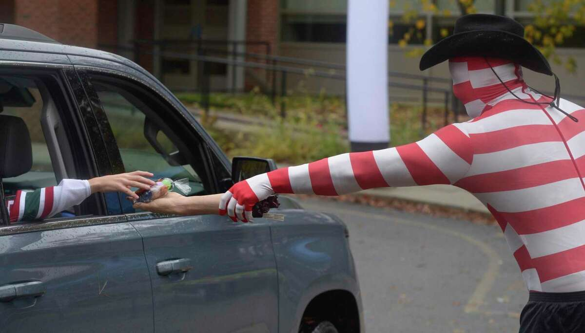 Kregg Zulkeski, from the Parks & Recreation department, hands out treats at the drive-thru Halloween event held at the Comstock Community Center on Friday afternoon, October 30, 2020, in Wilton, Conn.