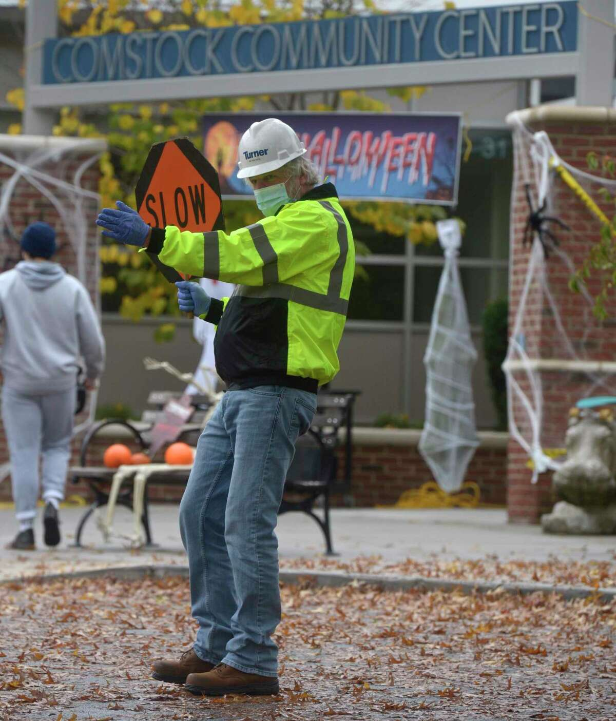 Steve Pierce, from the Parks & Recreation department, directs traffic at the drive-thru Halloween event held at the Comstock Community Center on Friday afternoon, October 30, 2020, in Wilton, Conn.