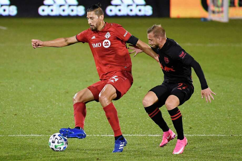 Toronto FC's Omar Gonzalez, left, controls the ball as New York Red Bulls' Daniel Royer defends earlier this month at Rentschler Field. Photo: Jessica Hill / Associated Press / Copyright 2020. The Associated Press. All rights reserved