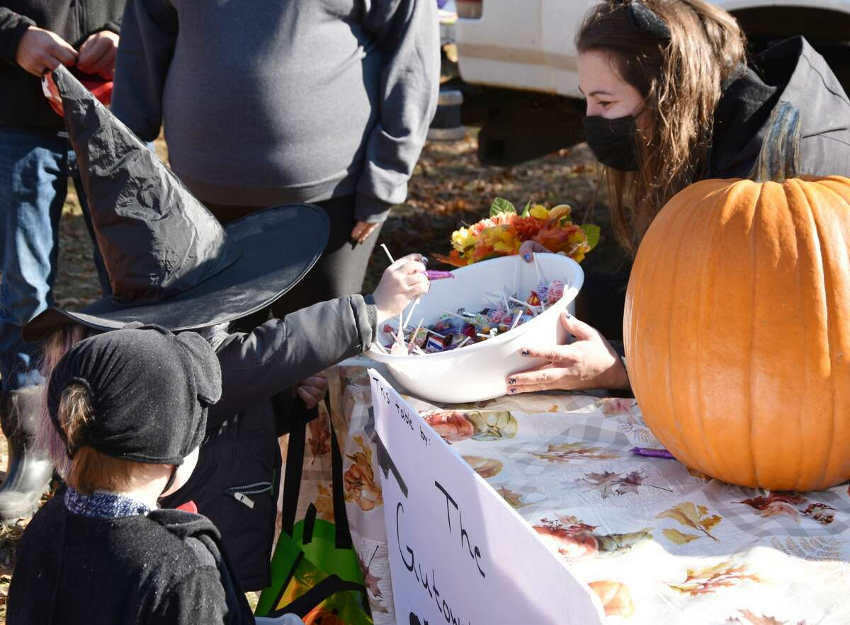 Ashley Gutowski, of the Brethren Boosters, offers some candy to a young witch on Saturday.