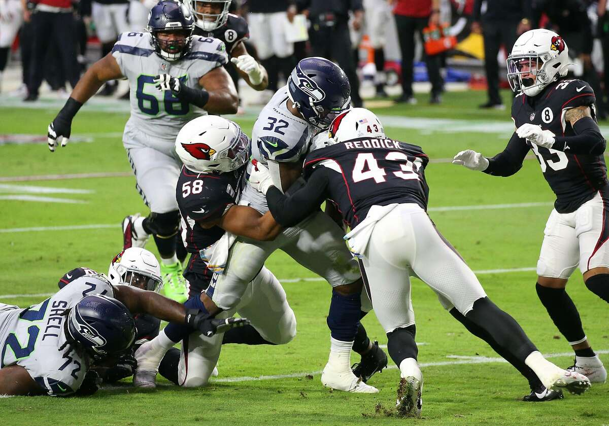 GLENDALE, ARIZONA - OCTOBER 25: Running back Chris Carson #32 of the Seattle Seahawks runs with the ball against linebacker Jordan Hicks #58 and linebacker Haason Reddick #43 of the Arizona Cardinals in the first quarter of the game at State Farm Stadium on October 25, 2020 in Glendale, Arizona. (Photo by Christian Petersen/Getty Images)