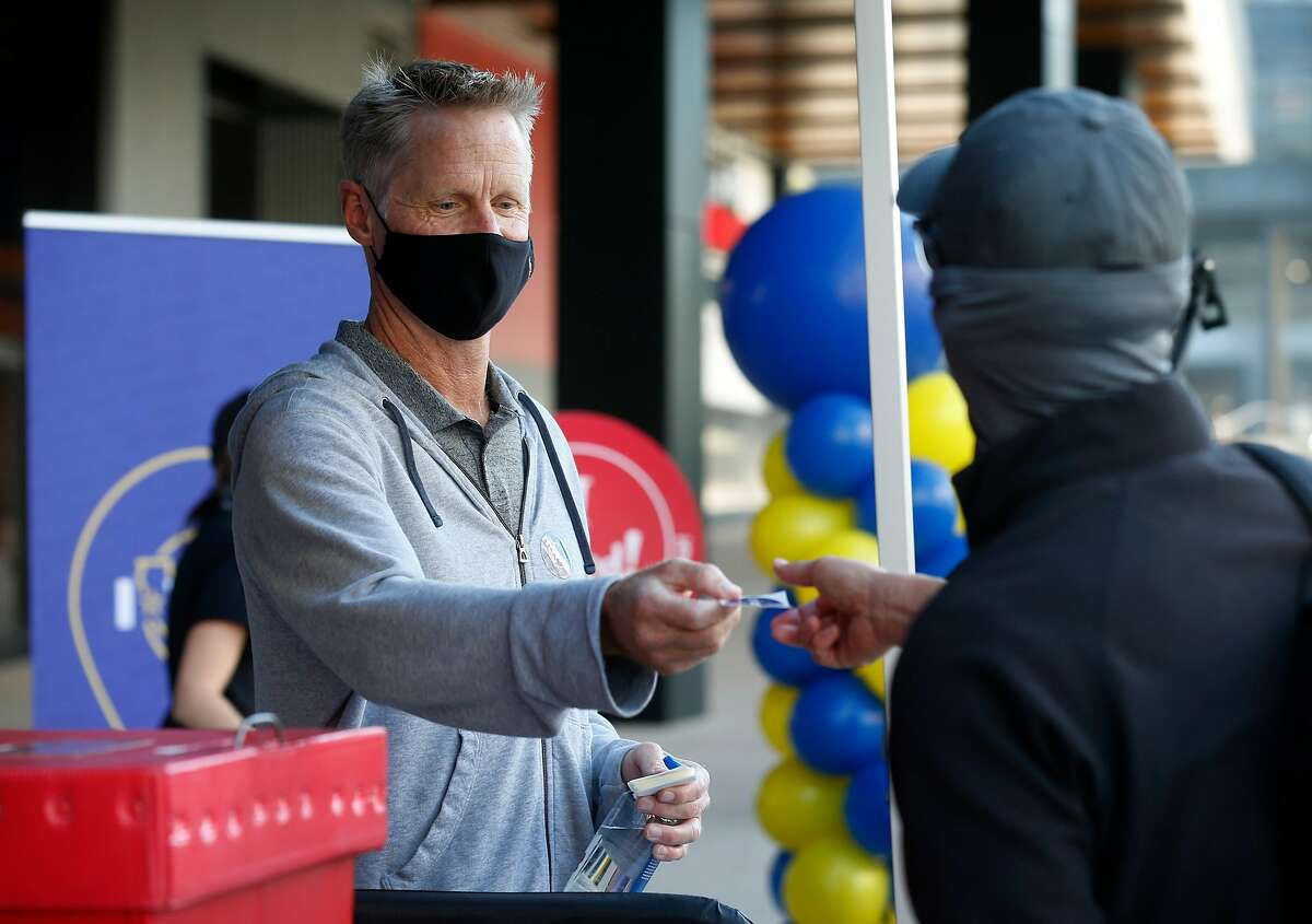 """Golden State Warriors head coach Steve Kerr hands an """"I Voted""""€� sticker to a voter dropping off a ballot at a walk-up collection point at Chase Center in San Francisco, Calif. on Saturday, Oct. 31, 2020."""