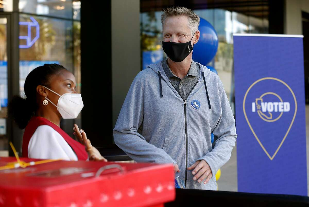 Golden State Warriors head coach Steve Kerr chats with poll worker Jujuana Williams after dropping off his ballot at a walk-up collection point at Chase Center in San Francisco.