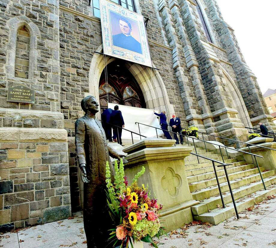"""New Haven, Connecticut - Friday, October 30, 2020: A portrait of Rev. Michael J. McGivney is unveiled Saturday in front of St. Mary's Church in New Haven during a Beatification Mass for McGivney, founder of the Knights of Columbus. The mass is video streamed from the Cathedral of St. Joseph in Hartford around the world and also televised at St. Mary's Church in New Haven as the Catholic Church Saturday declared Father McGivney, """"blessed"""", which, in the Catholic Church, is one step from canonization as a saint. McGivney died in 1890. Photo: Peter Hvizdak / Hearst Connecticut Media / New Haven Register"""