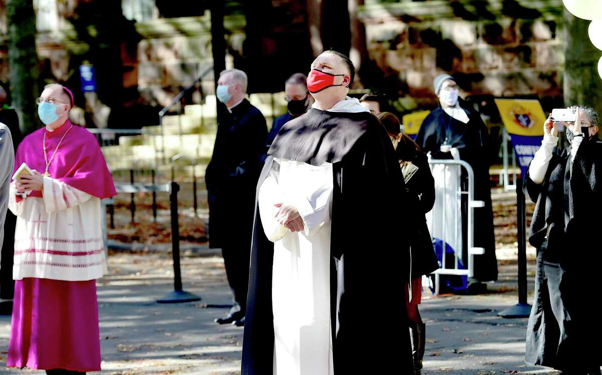 Bishop John Barres of the Diocese of Rockville Centre of Long Island, NY, left, and Father Jonathan Kalisch, prior of Dominican Community of St. Mary's Church, fourth from left, watch as a portrait of Rev. Michael J. McGivney is unveiled Saturday in front of St. Mary's Church in New Haven. Below, a procession outside the church.