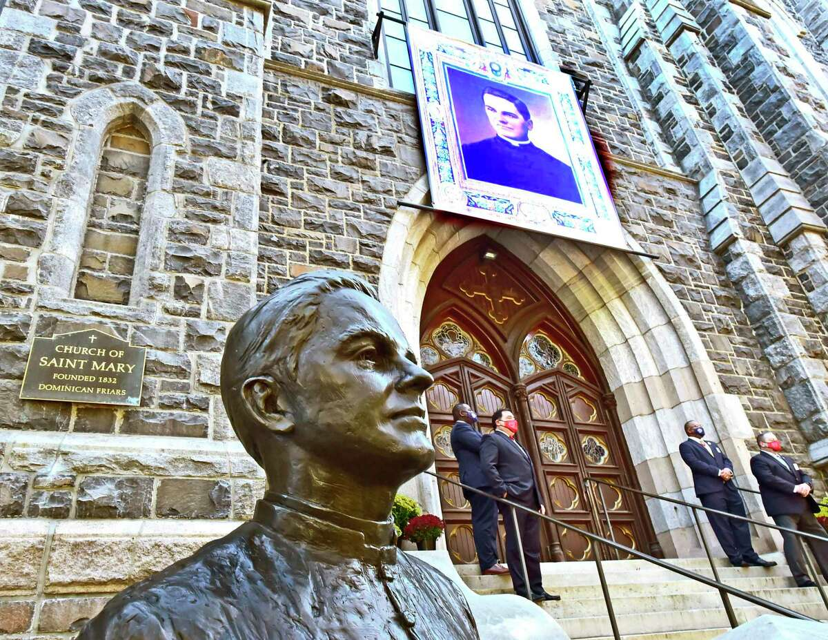 New Haven, Connecticut - Friday, October 30, 2020: A portrait of Rev. Michael J. McGivney is unveiled Saturday in front of St. Mary's Church in New Haven during a Beatification Mass for McGivney, founder of the Knights of Columbus. The mass is video streamed from the Cathedral of St. Joseph in Hartford around the world and also televised at St. Mary's Church in New Haven as the Catholic Church Saturday declared Father McGivney,