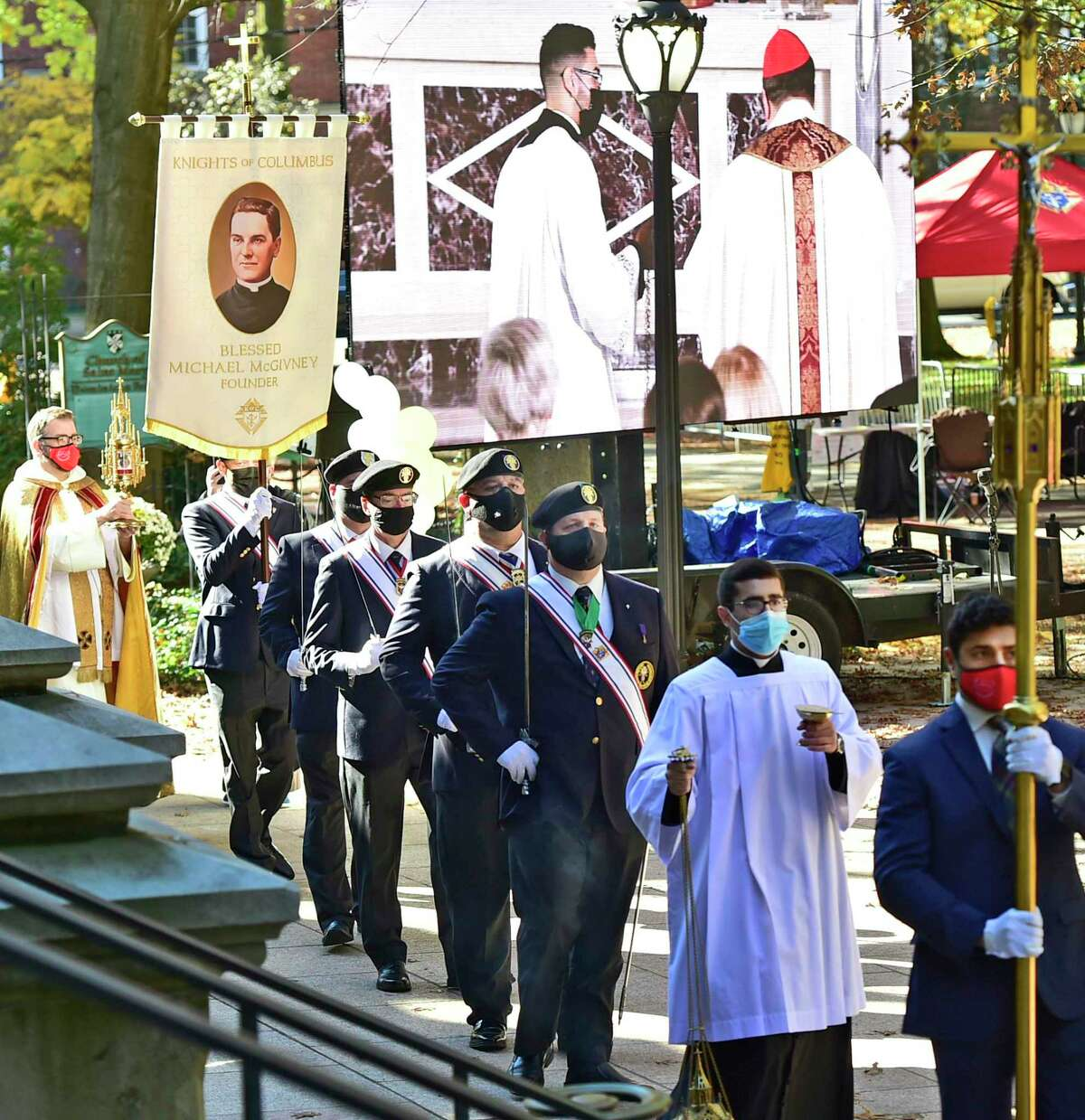 New Haven, Connecticut - Friday, October 30, 2020: A procession with a portion of an encased bone of Rev. Michael J. McGivney, founder of the Knights of Columbus at St. Mary's Church in New Haven, far left in photo, during a Beatification Mass for McGivney, that is video streamed Saturday from the Cathedral of St. Joseph in Hartford around the world and also televised at St. Mary's Church in New Haven as the Catholic Church Saturday declared Father McGivney,