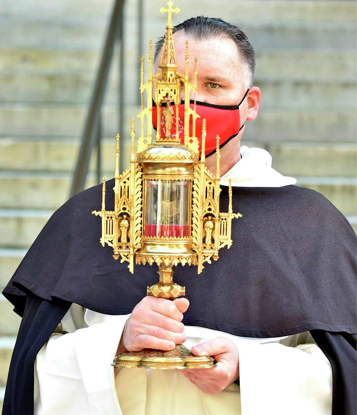 New Haven, Connecticut - Friday, October 30, 2020: Father Jonathan Kalisch, Prior of Dominican Community of St. Mary's Church, holds an encased portion of the backbone of Rev. Michael J. McGivney Saturday at St. Mary's Church in New Haven during a Beatification Mass for McGivney, founder of the Knights of Columbus. The mass is video streamed from the Cathedral of St. Joseph in Hartford around the world and also televised at St. Mary's Church in New Haven as the Catholic Church Saturday declared Father McGivney,