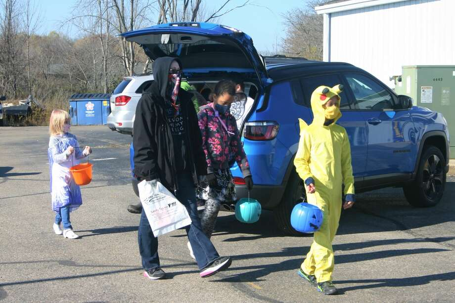 Children dressed in Halloween costumes collect treats as they participate in the Betten Baker Trunk-or-Treat on Saturday. Photo: Pioneer Photo/Cathie Crew