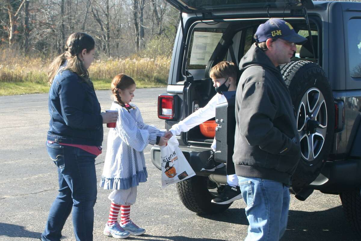 Children dressed in Halloween costumes collect treats as they participate in the Betten Baker Trunk-or-Treat on Saturday.