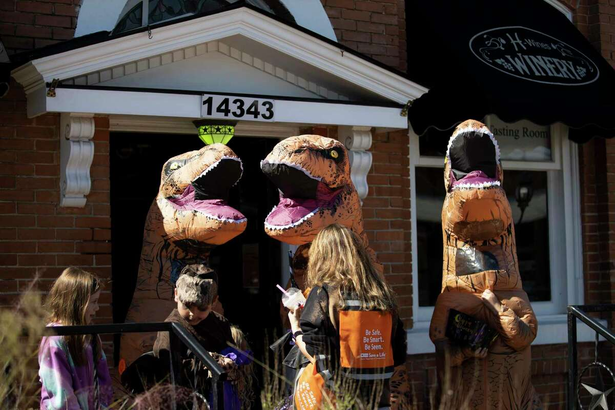 People dressed as dinosaurs in front of First State Bank hand out candy to children in Historic Montgomery, Saturday, Oct. 31, 2020. Event planners expected over 4,000 people to attend the annual event where participants were able to partake in traditional trick-or-treating despite the COVID-19 pandemic.