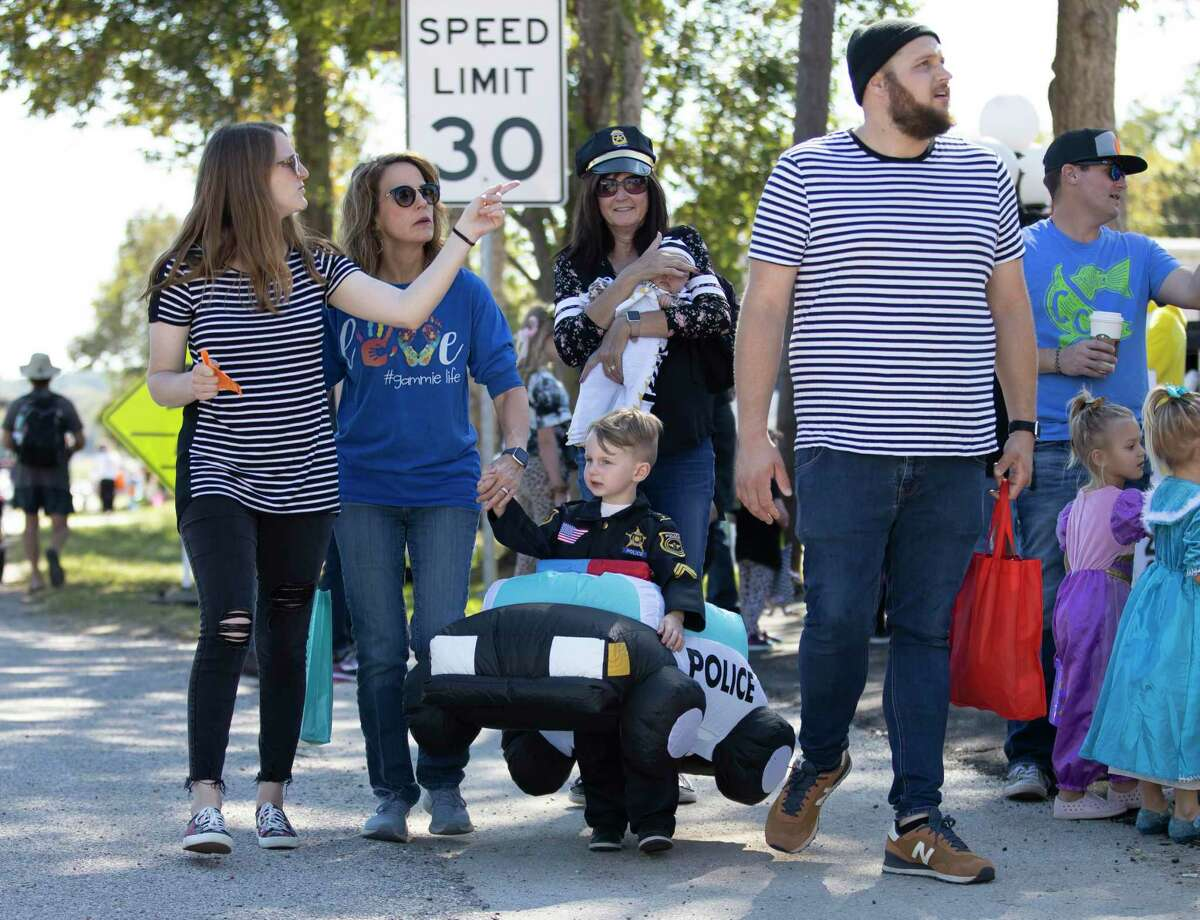Families walk down TX-149 in Historic Montgomery during a trick-or-treating Halloween event, Saturday, Oct. 31, 2020. Event planners expected over 4,000 people to attend the annual event where participants were able to partake in traditional trick-or-treating despite the COVID-19 pandemic.