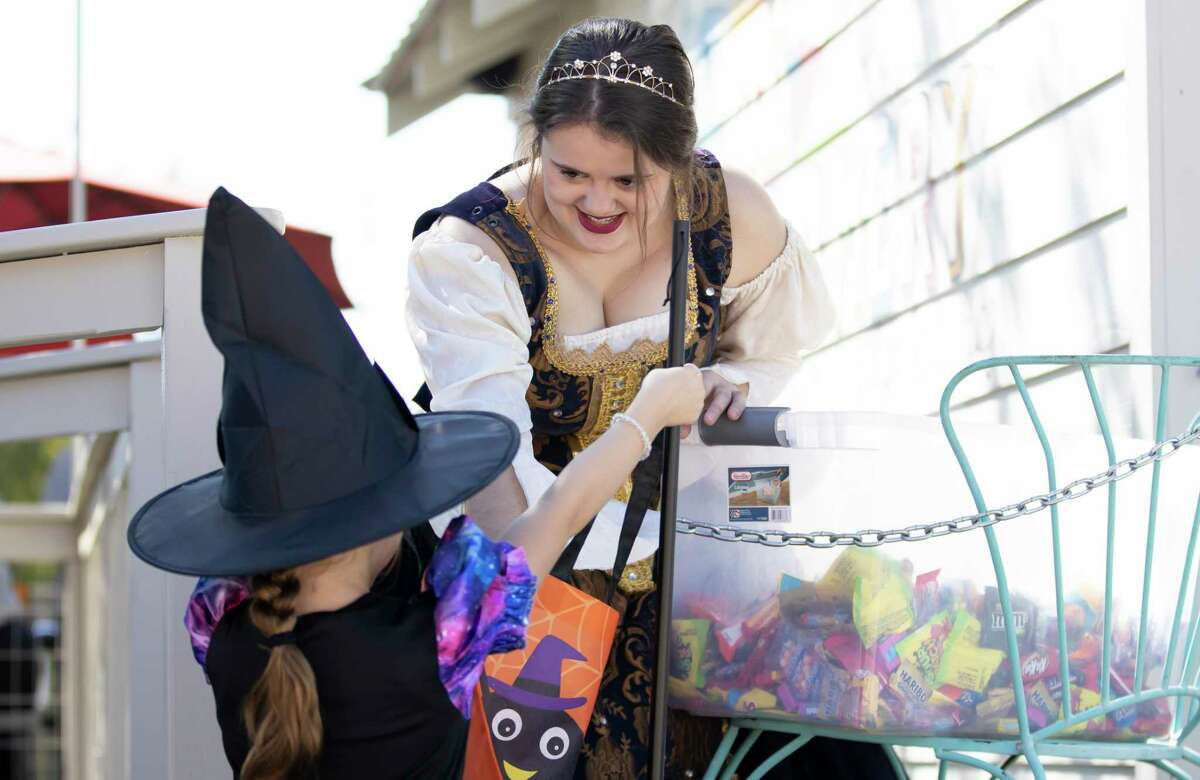 Kenzie Soape with Montgomery Original Snowballs hands out candy to children in Historic Montgomery, Saturday, Oct. 31, 2020. Event planners expected over 4,000 people to attend the annual event where participants were able to partake in traditional trick-or-treating despite the COVID-19 pandemic.