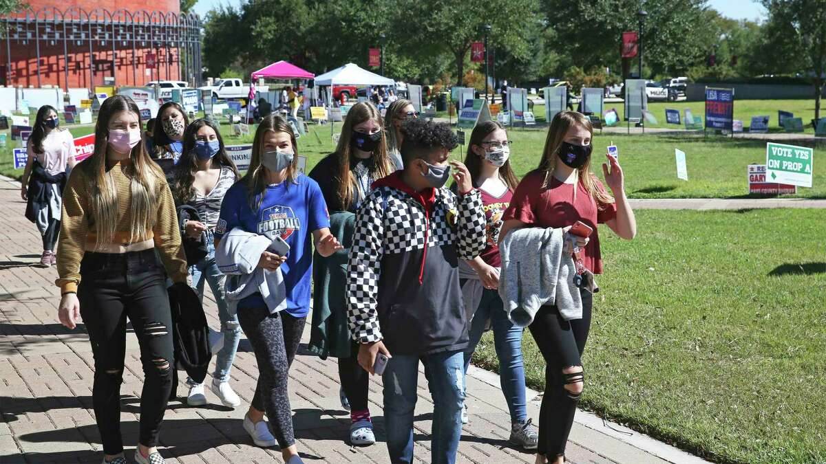 Students notice the electioneering as voters walk in to the polls on the campus of Texas State University on Oct. 30, 2020.