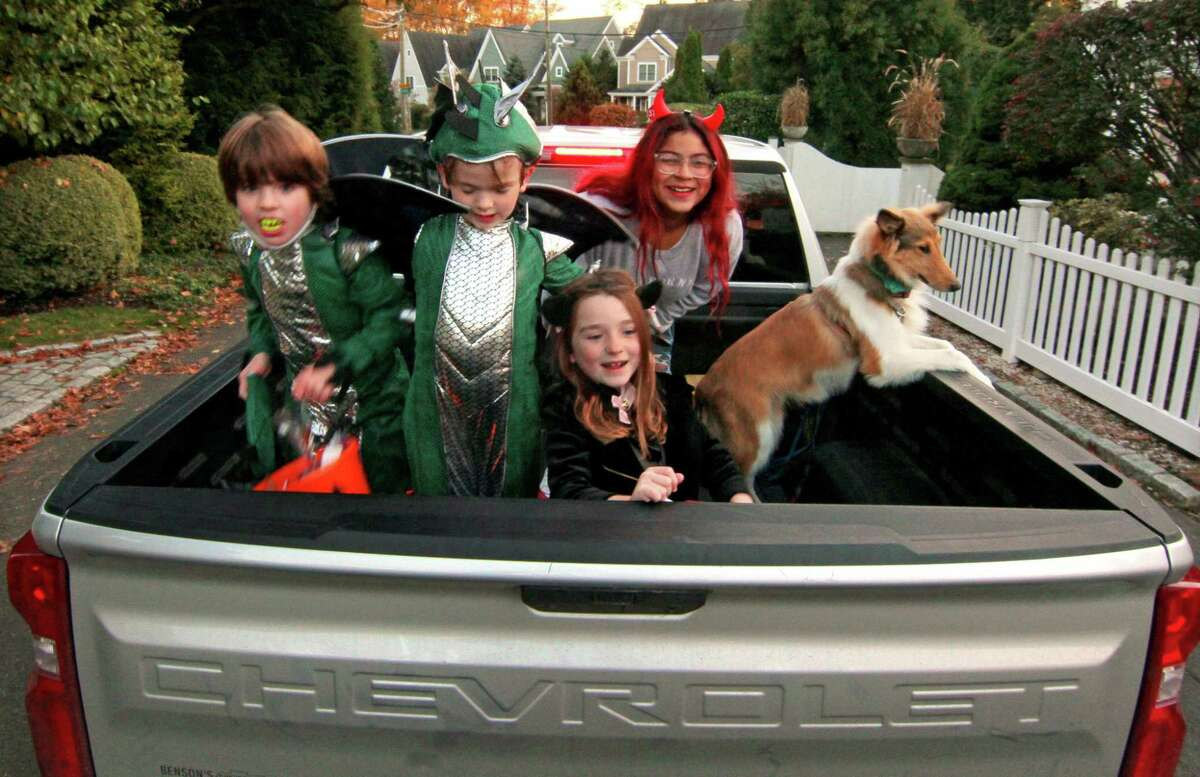 Children sit in the back of the family pickup truck as they go trick or treating in Rowayton on Saturday.
