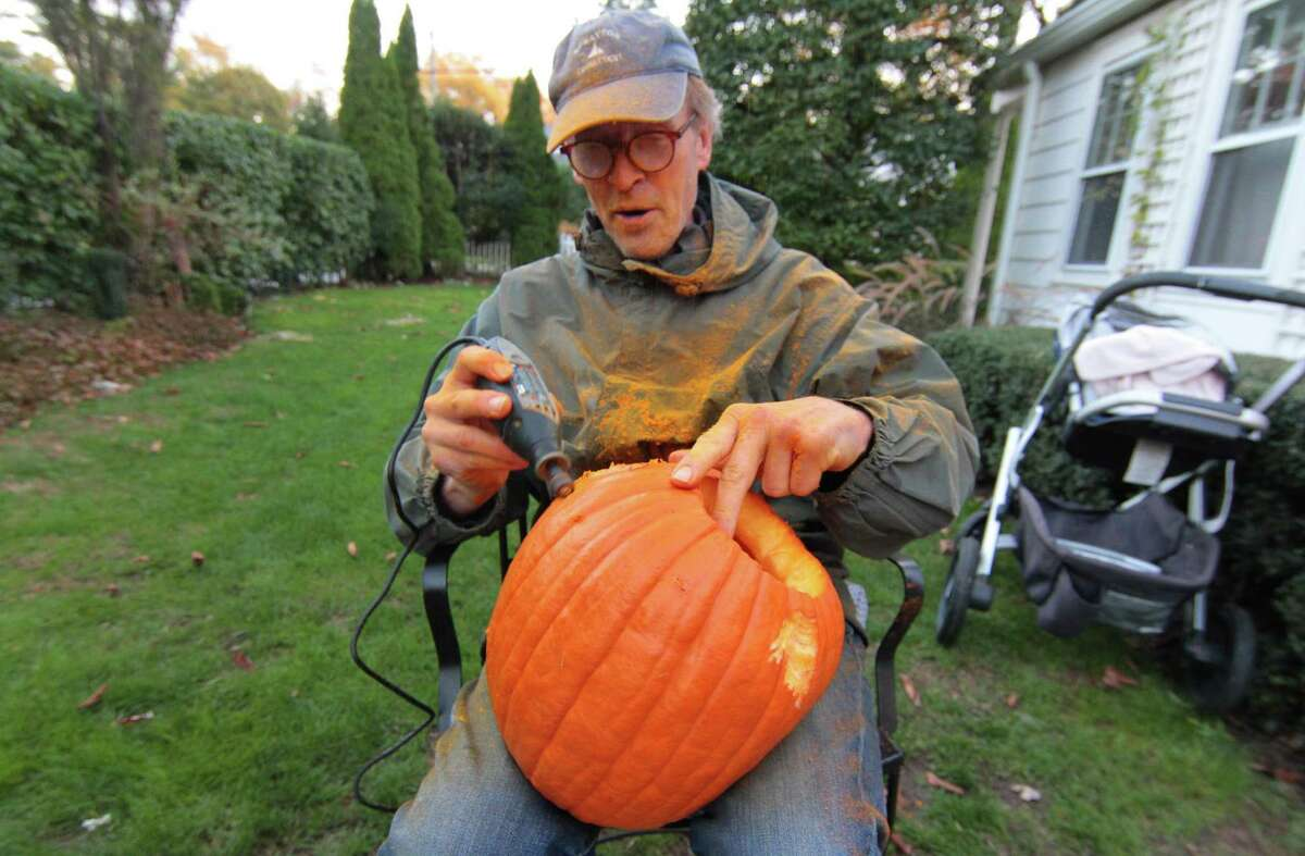 Brian Kammerer carves a pumpkin during Halloween Eve in Rowayton, Conn., on Saturday Oct. 31, 2020.
