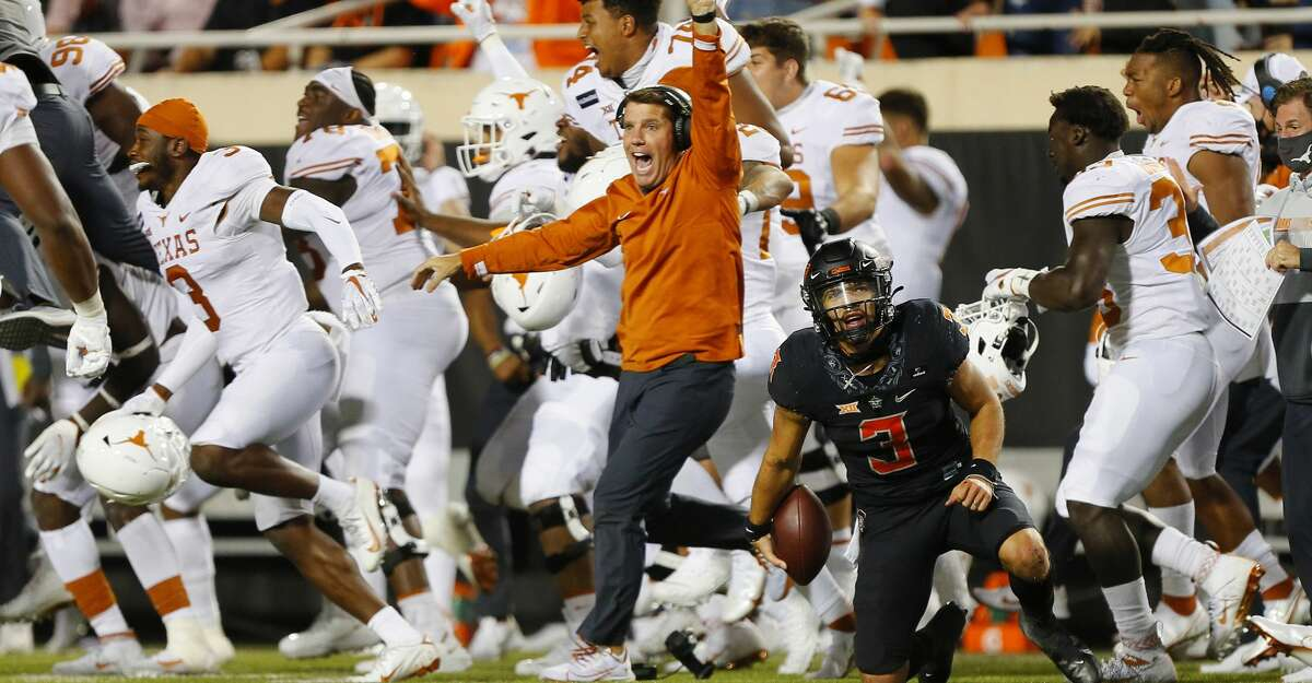 The Texas Longhorns celebrate their upset victory as quarterback Spencer Sanders #3 of the Oklahoma State Cowboys reacts after getting taken down on the final play in overtime against the Texas Longhorns at Boone Pickens Stadium on October 31, 2020 in Stillwater, Oklahoma. Texas won 41-34. (Photo by Brian Bahr/Getty Images)