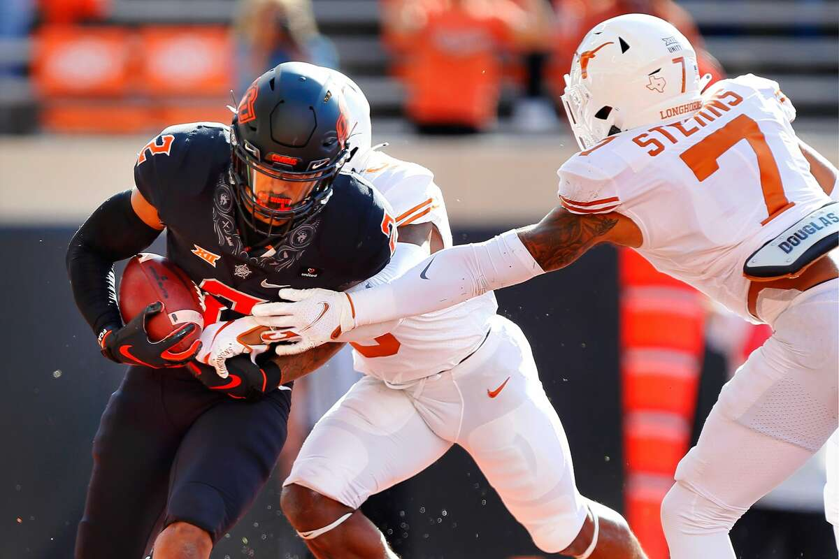 STILLWATER, OK - OCTOBER 31: Wide receiver Tylan Wallace #2 of the Oklahoma State Cowboys catches an 11-yard touchdown pass against defensive back Josh Thompson #9 and defensive back Caden Sterns #7 of the Texas Longhorns in the first quarter at Boone Pickens Stadium on October 31, 2020 in Stillwater, Oklahoma. (Photo by Brian Bahr/Getty Images)