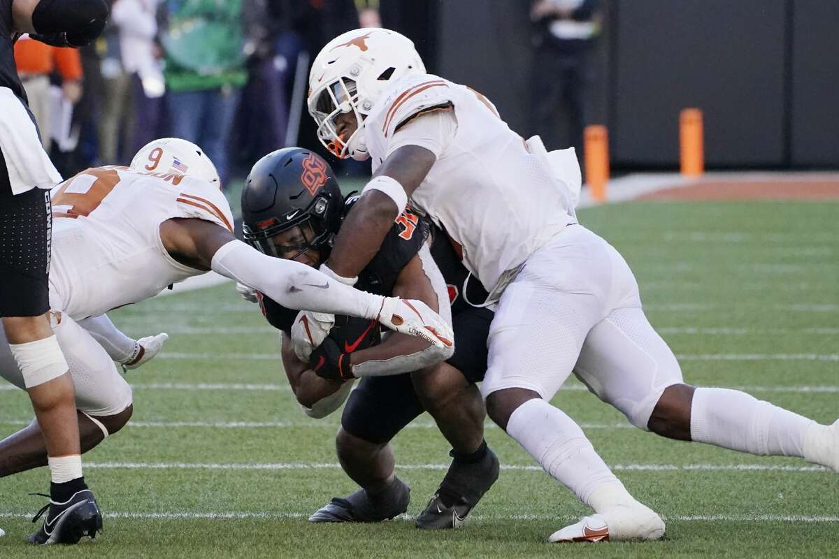 Oklahoma State running back Chuba Hubbard (30) is tackled by Texas defensive back Josh Thompson (9) and linebacker Juwan Mitchell, right, in the second half of an NCAA college football game in Stillwater, Okla., Saturday, Oct. 31, 2020. (AP Photo/Sue Ogrocki)