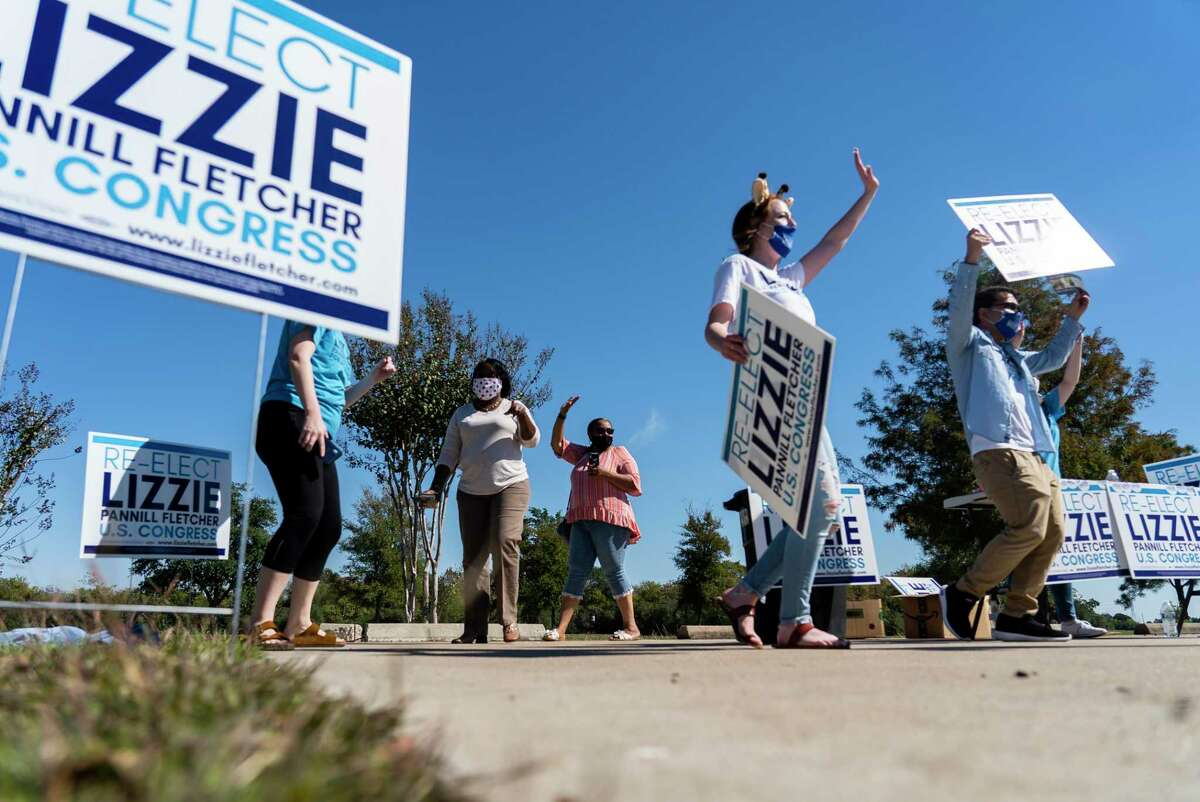 Campaign volunteers for Democratic U.S. Representative Lizzie Pannill Fletcher dance and wave at cars at a Halloween drive-through giveaway at the Weekly Community Center in Cypress on Saturday, Oct. 31.