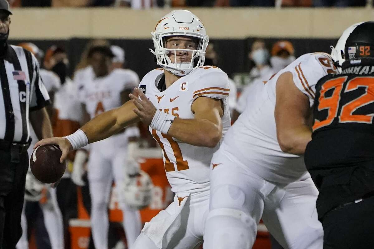 Texas quarterback Sam Ehlinger (11) throws a touchdown pass in overtime of an NCAA college football game against Oklahoma State in Stillwater, Okla., Saturday, Oct. 31, 2020. (AP Photo/Sue Ogrocki)